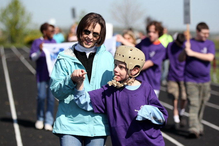 Carroll Springs School's Christine Paull helps Kyle Taylor, right, walk during the opening ceremony. (Jen Rynda/Patuxent Homestead)
