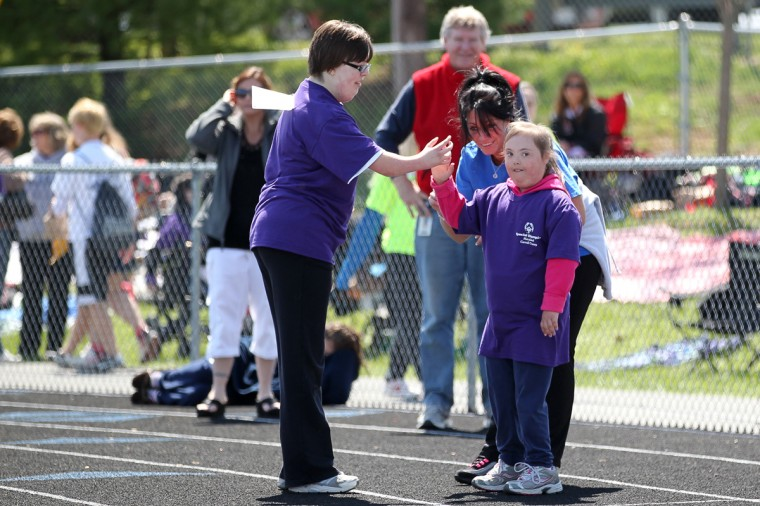 South Carroll High School's Isabelle Kawczynski, 14, gives a high five to Winfield Elementary School's Summer Salmon, 8, after Summer finished strong in her race. (Jen Rynda/Patuxent Homestead)