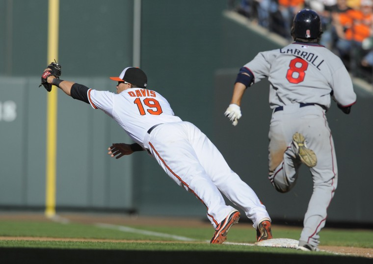 Orioles' first baseman Chris Davis, left, makes a diving catch at first on a throw from Mark Reynolds to get Jamey Carroll at first in the 8th inning. (Lloyd Fox/Baltimore Sun)