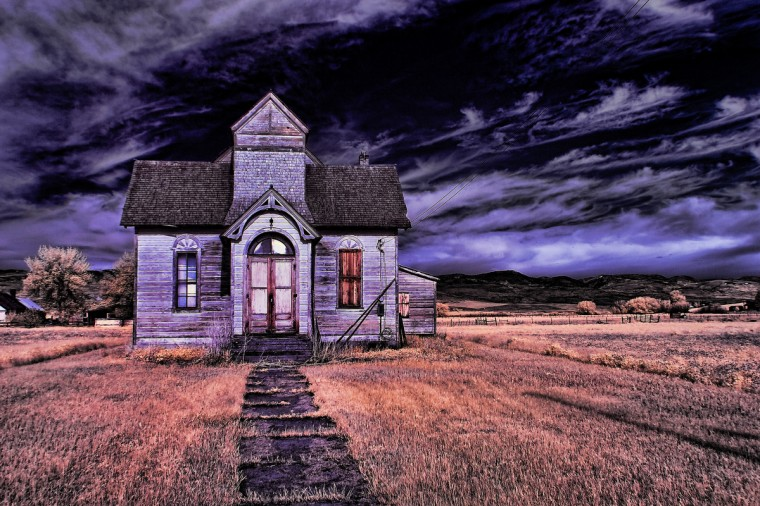 "Spooky: ""Haunted House?"" by John Jake Jakubik -- Jake shot ""Haunted House?"" with his Canon 20D modified to shoot color infrared. ""Coming from a journalistic background, I don't ordinarily care too much for over manipulated images. I tend to be more of a purist. But, considering the nature of our category this week, this photograph was right on the money. Obviously, the photographer is extremely good at crafting an interesting image through the use of software. But, the composition and use of the subject matter were also well executed."""