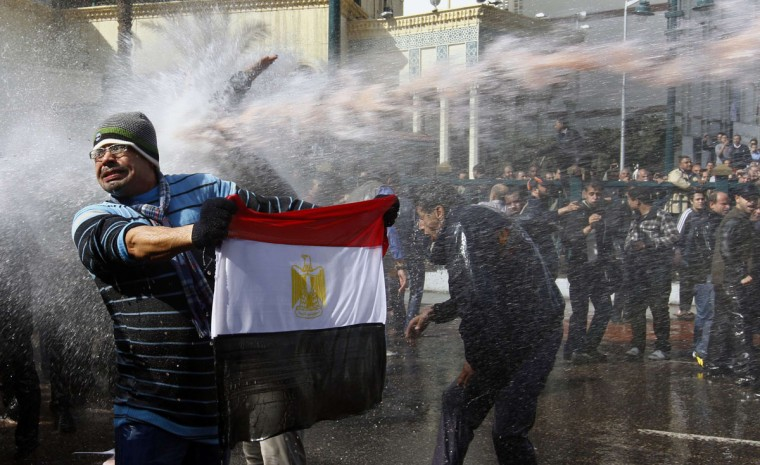 January 28, 2011: A protester holds an Egyptian flag as he stands in front of water canons during clashes in Cairo. (Yannis Behrakis/Reuters)