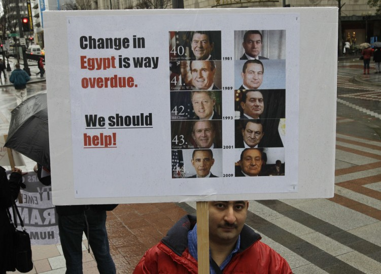 January 29, 2011: Mohamed Sadek, who is from Egypt, but lives in Redmond, Washington, holds a sign comparing the number of U.S. presidents who have been in power while Egyptian president Hosni Mubarakat has been in office, during a rally in downtown Seattle. Several hundred people gathered to show their support and solidarity for anti-government demonstrations in Egypt. (AP Photo/Ted S. Warren)