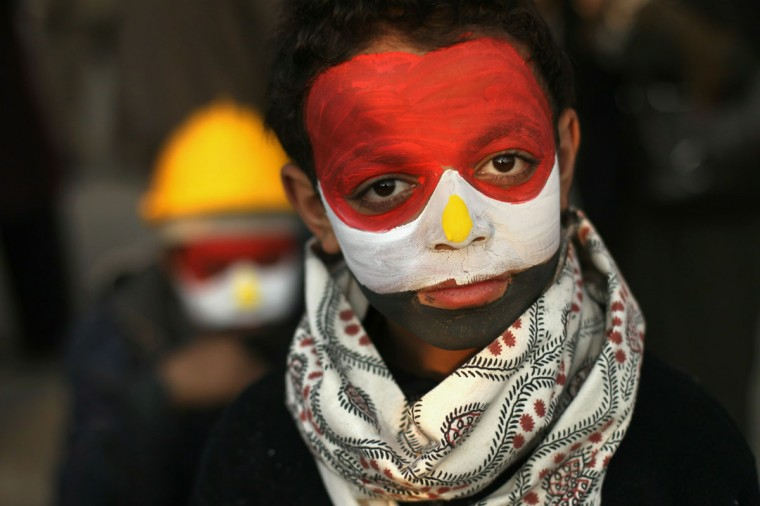 February 7, 2011: His face painted in the national colors, anti-government protester Mamoud Tariq, 13, attends a demonstration in Tahrir Square in Cairo, Egypt. Almost two weeks since the protests began, thousands of protesters continue to occupy the square, demanding the resignation of Egyptian President Hosni Mubarak. (John Moore/Getty Images)