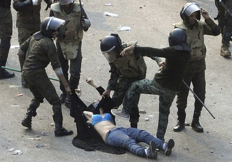 December 17, 2011: Egyptian army soldiers arrest a female protester during clashes at Tahrir Square in Cairo. Soldiers beat demonstrators with batons in a second day of clashes that have killed nine people and wounded more than 300, marring the first free election most Egyptians can remember. (Stringer/Reuters)