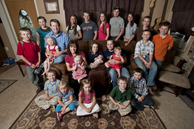 "As the matriarch of the Duggar household, Michelle (Center left-ish) exploded into the spotlight as the fertile and loving mother in TLC's ""19 Kids & Counting"" reality show. Pictured: The Duggars are photographed with their kids for their hit television show. (TLC/Beth Hall)"