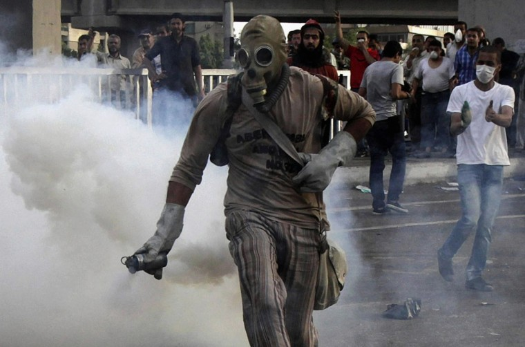 May 4, 2012: A protester catches a tear gas canister thrown by security forces near Egypt's Defense Ministry. Protesters threw rocks at troops guarding Egypt's defense ministry on Friday as thousands marched in Cairo to denounce violence against demonstrators and the exclusion of candidates from the presidential election. The crowd hurled projectiles and insults at the soldiers sent to defend the ministry after 11 people were killed in clashes there on Wednesday, and called for the overthrow of the head of the ruling army council, Field Marshal Hussein Tantawi. (Asmaa Waguih/Reuters)
