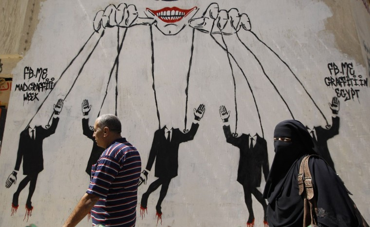 May 21, 2012: People walk near a graffiti depicting the military council using its power against citizens, near Tahrir square in Cairo. (Ammar Awad/Reuters)