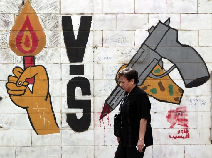 May 22, 2012: An Egyptian woman walks in front of a wall sprayed with graffiti depicting the ruling military council controlling the presidential elections in Cairo. (Amr Abdallah Dalsh/Reuters)