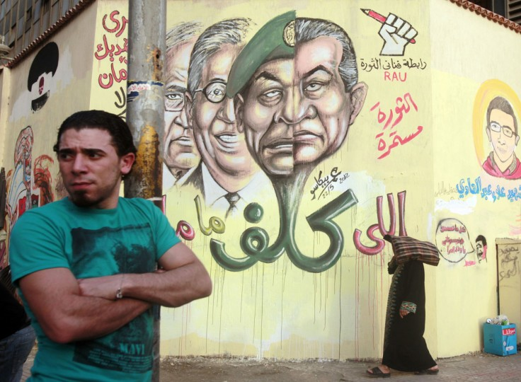 May 22, 2012: A man stands next to graffiti depicting former President Hosni Mubarak and several presidential candidates, at Tahrir square in Cairo. (Asmaa Waguih/Reuters)