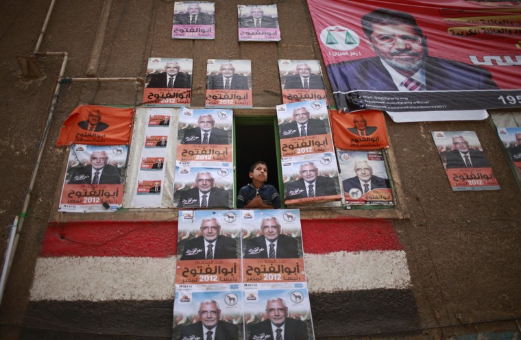 May 23, 2012: A boy looks out of a window covered with posters of presidential candidate Abdel Moneim Abol Fotouh in Cairo during presidential elections. (Suhaib Salem/Reuters)