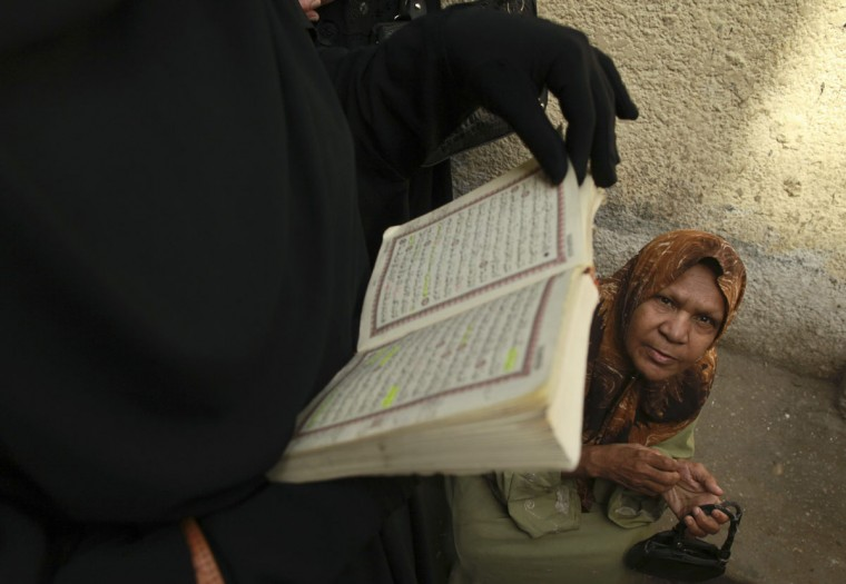 May 23, 2012: A woman reads the Koran as another one waits to casts her vote at a polling station in Cairo. (Mohammed Salem/Reuters)