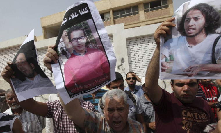 May 23, 2012: Men protesting against Egyptian presidential candidate Amr Moussa hold posters of their sons, killed during last year's revolution, outside a polling station in Cairo. (Amr Abdallah Dalsh/Reuters)