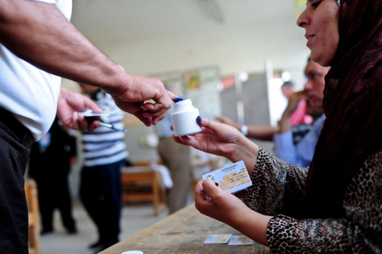 May 23, 2012: An Egyptian dips his finger into the ink after voting at a polling station in Cairo, capital of Egypt. Voters are obliged to dip a finger in permanent ink to keep anyone from voting twice during the presidential elections. (Qin Haishi/Xinhua/Zuma Press/MCT)