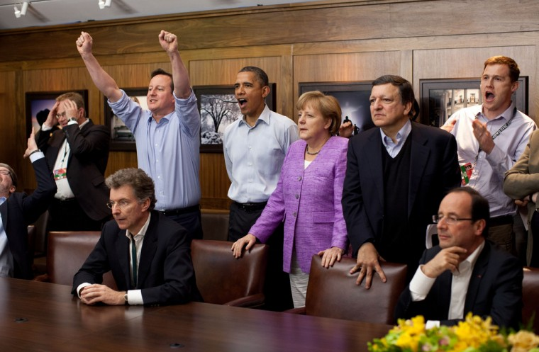Prime Minister David Cameron of the United Kingdom, President Barack Obama, Chancellor Angela Merkel of Germany, José Manuel Barroso, President of the European Commission, and others watch the overtime shootout of the Chelsea vs. Bayern Munich Champions League final, in the Laurel Cabin conference room during the G8 Summit at Camp David, Md., May 19, 2012. (Pete Souza/White House)