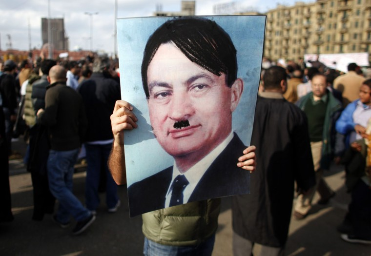 January 31, 2011: A man carries a picture depicting Egyptian President Hosni Mubarak as Adolf Hitler during a protest in Cairo. Mubarak overhauled his government on Monday to try to defuse a popular uprising against his 30-year rule but angry protesters rejected the changes and said he must surrender power. (Goran Tomasevic/Reuters)
