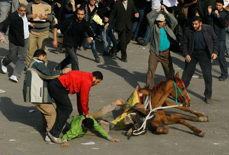 February 2, 2011: A supporter of embattled Egyptian president Hosni Mubarek is thrown from a horse during a clash between pro-Mubarek and anti-government protesters in Tahrir Square in Cairo, Egypt. Yesterday President Mubarak announced that he would not run for another term in office, but would stay in power until elections later this year. Thousands of supporters of Egypt's long-time president and opponents of the regime clashed then today in Tahrir Square, throwing rocks and fighting with improvised weapons. (Chris Hondros/Getty Images)