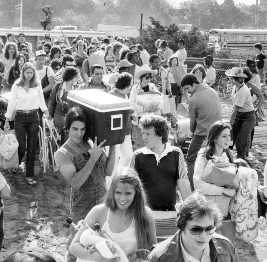 Preakness goers enter the infield with coolers and supplies before the 1980 race. (Clarence Garrett/Baltimore Sun)