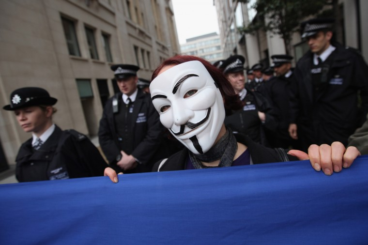 An anti-capitalist protester from the 'Occupy' movement holds a banner in front of police officers during a demonstration in London, England. Students, trade unionists, pensioners and activists from the anti-capitalist 'Occupy' movement marched through the centre of London before congregating and staging a demonstration in Trafalgar Square to mark May Day. (Dan Kitwood/Getty Images)