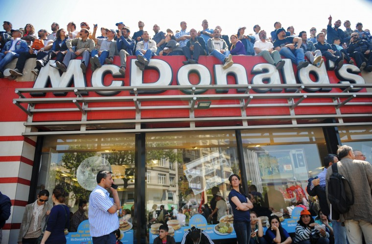 People sit on top of a McDonalds restaurant to watch a May Day rally in central Istanbul. Tens of thousands of workers gathered on an iconic square in the heart of Turkey's biggest city Istanbul to celebrate May Day. (Bulent Kilic/AFP/GettyImages)