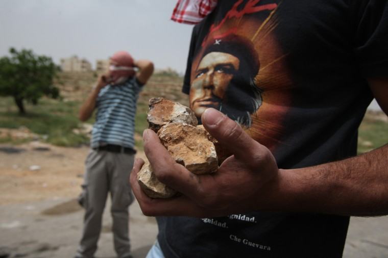 "A Palestinian protester, wearing a T-shirt bearing a portrait of Che Guevara, carries stones during clashes with Israeli troops outside Ofer military prison near the West Bank city of Ramallah following a demonstration in support for prisoners held in Israeli jails. Clashes erupted between stone-throwing youths and the Israeli army, who fired tear gas, rubber bullets and a foul-smelling liquid known as ""skunk"" to break up the demonstration. (Abbas Momani/AFP/GettyImages)"