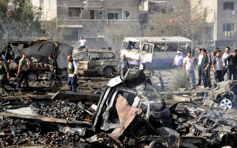 Security forces inspecting the site of twin blasts in Damascus. Two powerful blasts struck Damascus during morning rush hour, killing scores, wounding dozens and prompting the UN observer chief to appeal for help to end the bloodshed ravaging Syria. (Syrian Arab News Agency/Getty)