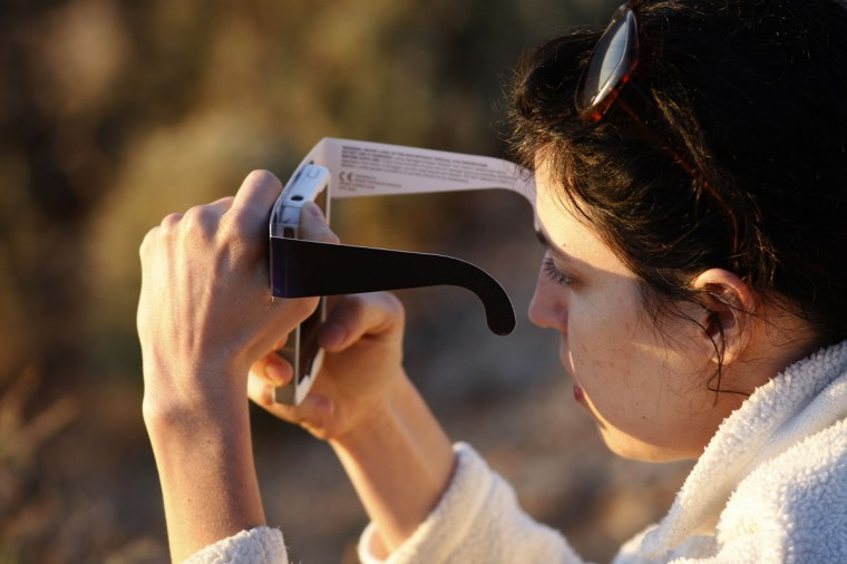 A woman checks her smart phone while watching the first annular eclipse seen in the U.S. since 1994 with special glasses to protect her eyes on May 20, 2012 in Grand Canyon National Park, Arizona. (David McNew/Getty Images)