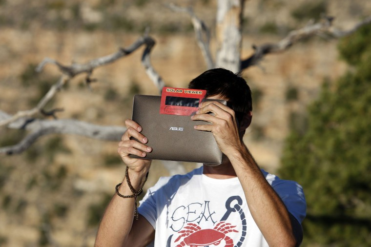A man uses solar film over the lens of his electronic device to photograph the first annular eclipse seen in the U.S. since 1994 on May 20, 2012 in Grand Canyon National Park, Arizona. (David McNew/Getty Images)