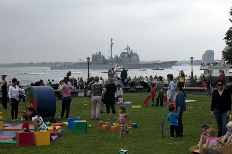 People watch from a lawn in Battery park as the USS San Jacinto (CG 56) passes the Statue of Liberty on the Hudson River during the Parade of Ships for the start of Fleet Week May 23, 2012 in New York City. (Allison Joyce/Getty Images)