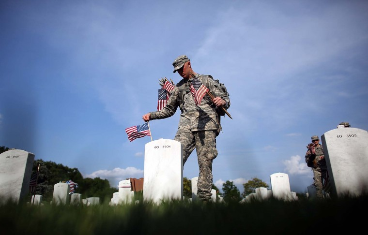 Members of the 3rd U.S. Infantry Regiment place American flags at the graves of U.S. soldiers buried in Section 60 at Arlington National Cemetery in preparation for Memorial Day May 24, 2012 in Arlington, Virginia. 'Flags-In' has become an annual ceremony since the 3rd U.S. Infantry Regiment (The Old Guard) was designated to be an Army's official ceremonial unit in 1948. Every available soldier in the 3rd U.S. Infantry Regiment participates in these events. (Win McNamee/Getty Images)