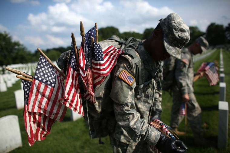 Members of the 3rd U.S. Infantry Regiment place American flags at the graves of U.S. soldiers buried in Section 60 at Arlington National Cemetery in preparation for Memorial Day May 24, 2012. (Win McNamee/Getty Images)