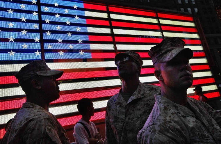 U.S. Marines look on in front of a lighted American flag in Times Square during Fleet Week festivities on May 26, 2012 in New York City. Fleet week, which has been held in New York City since 1984, celebrates the U.S. Navy and Marines Corps with a week of ship visitations and military demonstrations. Fleet Week concludes on Memorial Day with a military flyover to honor those killed while serving in the military. (Mario Tama/Getty Images)
