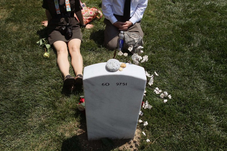 Two people site by a grave in Section 60 on Memorial Day at Arlington National Cemetery on May 28, 2012 in Arlington, Virginia. (Mark Wilson/Getty Images)