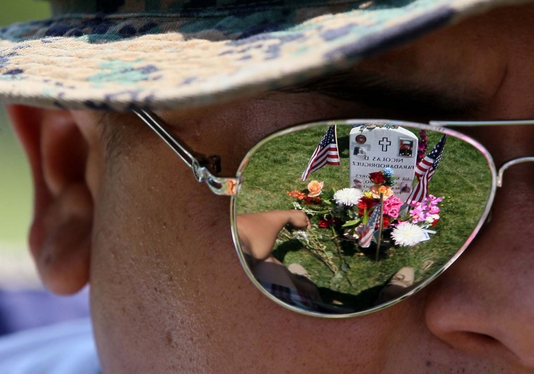 Ricky Parada sits at the grave of his little brother Cpl. Nicolas D. Paradarodriguez who was killed in Afghanistan, at Section 60 on Memorial Day at Arlington National Cemetery on May 28, 2012. (Mark Wilson/Getty Images)