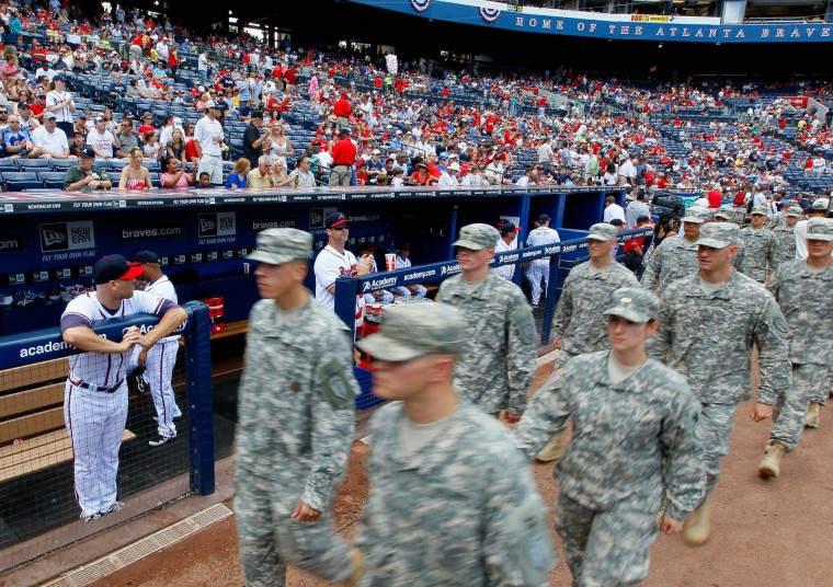 Members of the military walks past Tim Hudson #15 of the Atlanta Braves during the Memorial Day celebration prior to the game against the St. Louis Cardinals at Turner Field on May 28, 2012 in Atlanta, Georgia. (Kevin C. Cox/Getty Images)