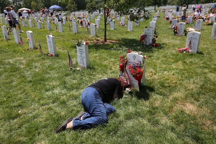 """Karen Clarkson lies over her slain son's grave at the National Cemetery on Memorial Day May 28, 2012 in Arlington, Virginia. Her son Sgt. Joel Clarkson was serving as an Army Ranger team leader in Afghanistan when he was shot and killed in March, 2010. Karen was one of some 1,200 adults, most of whom are grieving parents and spouses, who attended the TAPS National Military Survival Seminar held concurrently with a """"Good Grief Camp"""" for military children in Arlington. (John Moore/Getty Images)"""