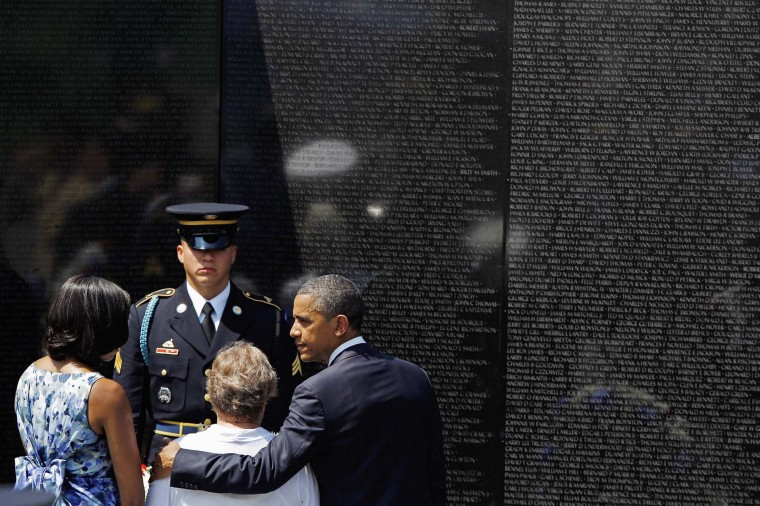 """U.S. President Barack Obama and first lady Michelle Obama (L) help Rose Mary Sabo-Brown place a wreath at the Vietnam Veterans Memorial during a Memorial Day ceremony on the National Mall May 28, 2012 in Washington, DC. Sabo-Brown is the widow of Army Specialist Leslie H. Sabo, Jr., who was posthumously awarded the Medal of Honor by Obama earlier this month. Today's ceremony at the memorial is the first event in the ongoing, 13-year Vietnam 50th Anniversary Commemoration Program that, according to the Department of Defense, """"will partner with other federal agencies, veterans groups, state, local government and non-government organizations to thank and honor veterans of the Vietnam War."""" (Chip Somodevilla/Getty Images)"""