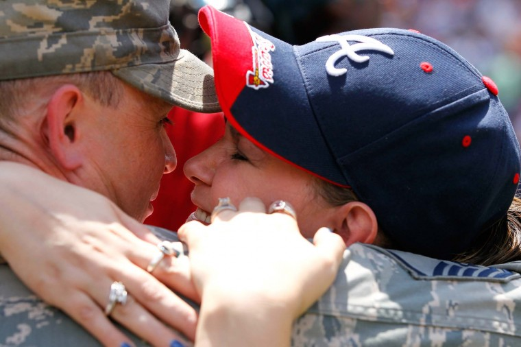 Master Sergeant David Sims is reunited with his wife Robin and his family during the fifth inning of the Memorial Day celebration between the Atlanta Braves and the St. Louis Cardinals at Turner Field on May 28, 2012 in Atlanta, Georgia. (Kevin C. Cox/Getty Images)