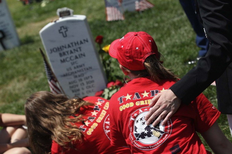 """Breanna McCain, 18, looks upon her father's grave at the National Cemetery on Memorial Day on May 28, 2012 in Arlington, Virginia. Her dad, Army SFC Johnathan McCain, was killed by a roadside bomb in Afghanistan in November 2011. Breanna came with her mother and three sisters to take part in a TAPS """"Good Grief Camp"""". (John Moore/Getty Images)"""