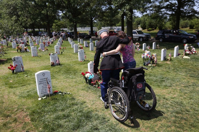 U.S. Marine Cpl. Miroslav Kazimir stands up with the help of his wife Marcela while visiting a grave at the National Cemetery on Memorial Day on May 28, 2012 in Arlington, Virginia. He had come to visit the grave of Marine Sgt. Sean Callahan who died in an IED attack in Afghanistan in April, 2011, the same attack that severely damaged both of Zazimir's legs. He is currently undergoing long-term therapy at the military hospital in Bethesda, MD. (John Moore/Getty Images)