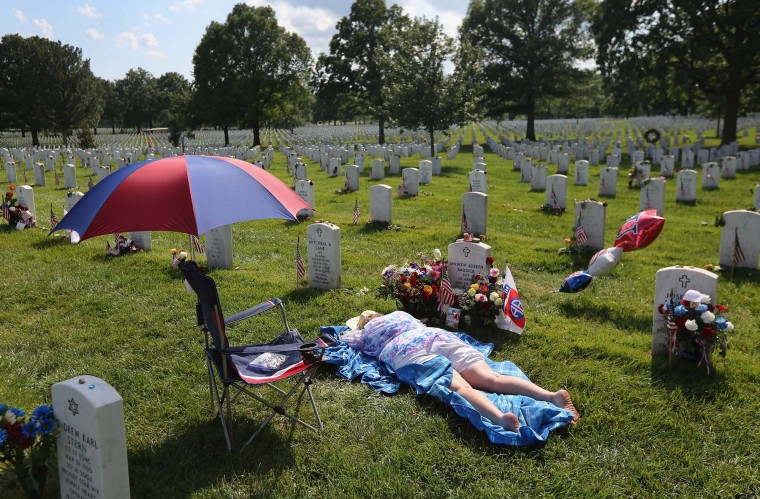 Ann Adams lies atop the grave of her son Army Sgt. Andrew Baddick at the National Cemetery on Memorial Day on May 28, 2012 in Arlington, VA. Baddick died while saving a comrade from drowning after a military vehicle rolled into a culvert in Iraq in 2003. (John Moore/Getty Images)