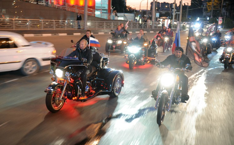 """August 2011: Russian Prime Minister Vladimir Putin (L) rides a motorbike as he takes part in the 16th annual motorbike festival held by """"The Night Wolves"""" youth organization in the southern Russian town of Novorossiysk, August 29, 2011. (Alexey Druzhinin/AFP/Getty Images)"""