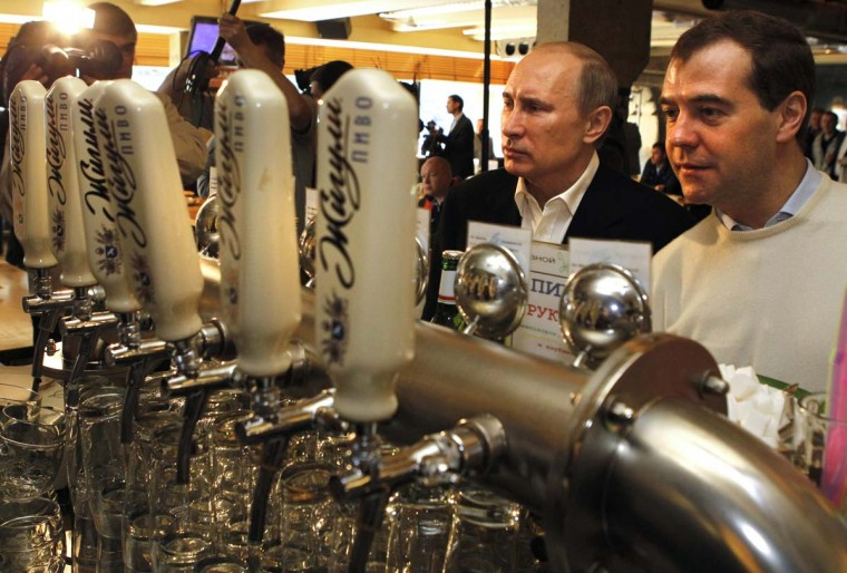 2012: Russian President Dmitry Medvedev (R) and President-elect Vladimir Putin (L) look at beer pumps in a bar after the celebration of the May Labour Day rally of the Russian Trade Unions and United Russia party in Moscow on May 1, 2012. (Dmitry Astakhov/AFP/Getty Images)