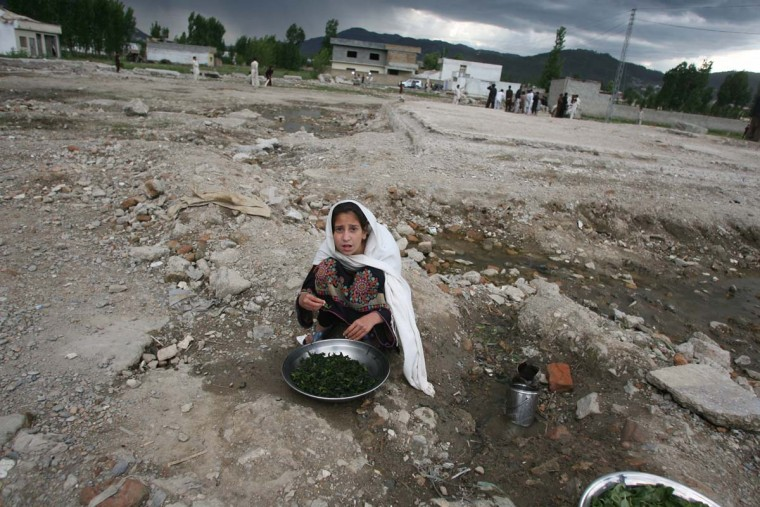A Pakistani girl washes vegetables at the site of the demolished compound of slain al-Qaida leader Osama bin Laden in northern Abbottabad on May 1, 2012. (Sajjad Qayyumsa/AFP/Getty Images)