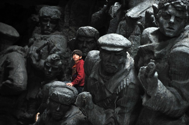 May 9, 2012: A boy climbs on a World War II monument at an open air museum in Kiev, Ukraine during Victory Day celebrations. (Sergei Supinsky/AFP/GettyImages)