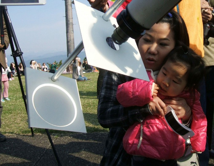 A girl with her mother observe a solar eclipse, focused onto a white background through a telescope, at Takayama village in Gunma prefecture, north of Tokyo on May 21, 2012. (Jiji Press/AFP/Getty Images)