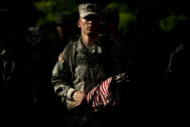 A soldier holds flags at Section 60, an area largely used for those who died while serving in the wars in Afghanistan and Iraq, at Arlington National Cemetery May 24, 2012 in Washington, DC. (Brendan/Smialowski/AFP/Getty Images)