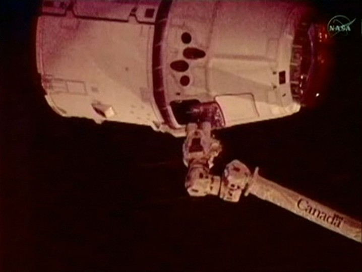 In this frame grab from a NASA video, the robotic arm (bottom) of the International Space Station captures the SpaceX Dragon capsule. The successful maneuver makes SpaceX the first private company to rendezvous with the orbiting lab. (NASA/AFP Photo/GettyImages)
