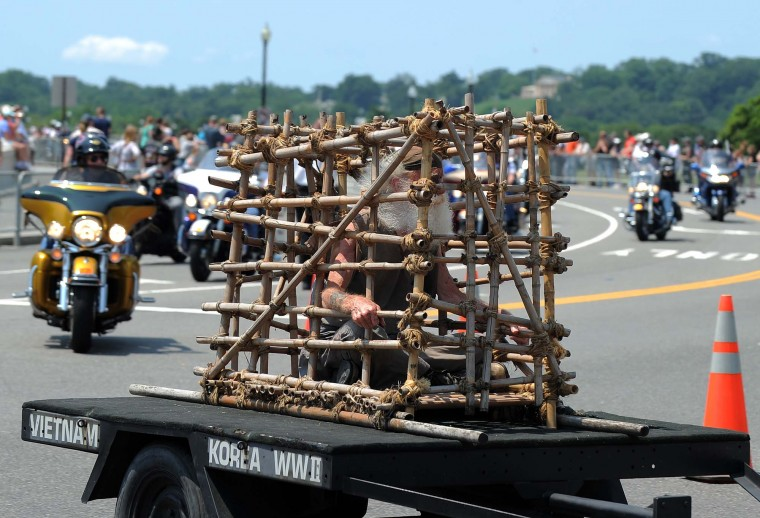 A man sits inside a bamboo cage, representing a prisoner of war as he is pulled on a trailer during Rolling Thunder 2012 in Washington, DC, on May 27, 2012. The 25th Annual Rolling Thunder rumbled into town to show support for veterans past and present, those who have fallen in war and those who are missing in action. (Jewel Samad/AFP/Getty Images)