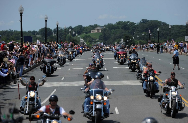 People wave as motorcyclists ride across the Memorial Bridge during Rolling Thunder 2012 in Washington, DC, on May 27, 2012. (Jewel Samad/AFP/Getty Images)