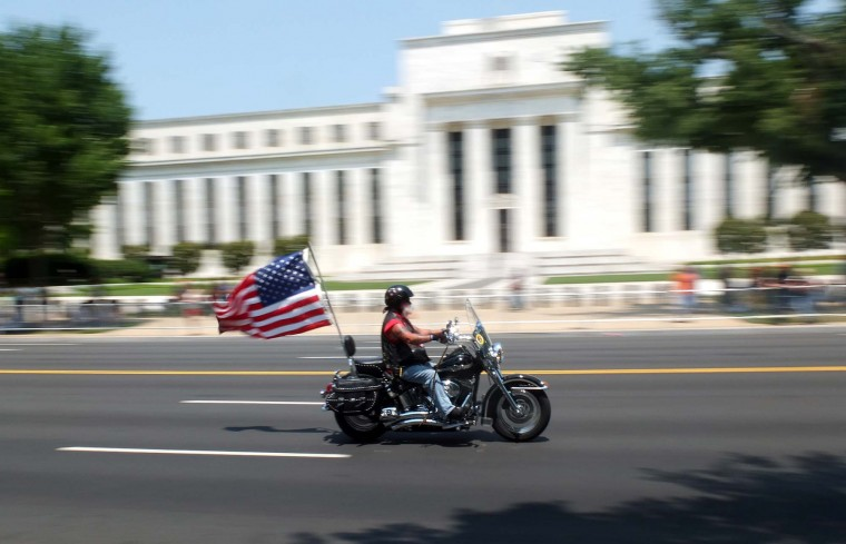 A motorcyclist rides waving a U.S. flag on Constitution Avenue during Rolling Thunder 2012 in Washington, DC, on May 27, 2012. (Mladen Antono/AFP/Getty Images)